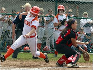 Southview's Katie Austin (20) scores against Elyria catcher Haley Looney (24) during the third inning of a Division I regional softball final Saturday  in Clyde, Ohio. Elyria defeated Southview 7-4.