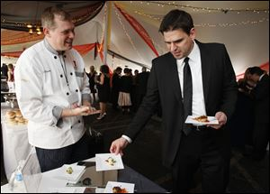 Greg Helyer selects some offerings from Toledo Club Chef Mike Rosendaul at Taste of the Nation.