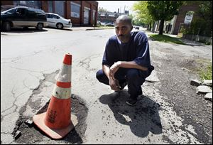 Damon McCullough recently placed an orange cone in a large pothole on West Delaware Avenue in Toledo. Mr. McCullough, who lives on the street, said he has complained to the city about its condition.