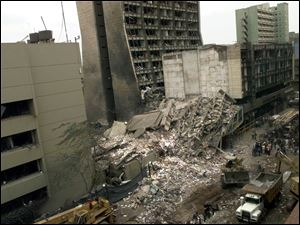 "This Aug. 8, 1998, file photo shows the United States Embassy, left, and other damaged buildings in downtown Nairobi, Kenya, the day after terrorist bombs in Kenya and Dar es Salaam, Tanzania. Among those killed in Kenya that day were Uttmalal ""Tom"" Shah and Molly Huckaby Hardy, who were working undercover for the CIA. In Al-Qaida's war on the United States, they are believed to be the first CIA casualties, and like many CIA officers, their service remained a secret in both life and death, marked only by anonymous stars on the wall at CIA headquarters and blank entries in its book of honor."