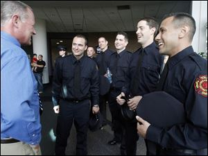 Lt. Michael Roemmele, retired, left, who is part of the Fire & Rescue Training Academy Staff, speaks with a few of his students before the graduation ceremony of the 2011 Toledo Fire & Rescue Training Academy class on Tuesday.