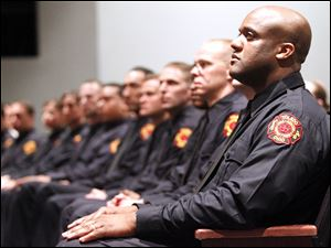 Sheldon Collins, right, listens to Mayor Mike Bell speaking during the graduation ceremony of the 2011 Toledo Fire & EMS class at Owens Community College.