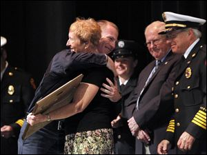 David Ferguson, left, accepts the John H. Brancheau Award from Mrs. Judy Brancheau, right, during the graduation ceremony of the 2011 Toledo Fire & Rescue Training Academy class at Owens Community College. Fire Chief Michael Wolever, far right, and Robert Schwanzl, Retired Assistant Chief, center right, stand nearby.