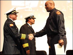 Chief Michael Wolever, left, shakes hands with Sheldon Collins, right, during the graduation ceremony of the 2011 Toledo Fire & Rescue Training Academy class at Owens Community College.