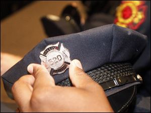 Sheldon Collins pins on his new fire badge during the graduation ceremony.
