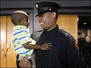 Andrew Hague, right, gives a big smile to nephew Anthony Richardson, left, after  the graduation ceremony of the 2011 Toledo Fire & Rescue Training Academy class at Owens Community College.