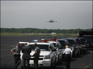 Air Force One approaches Toledo Express Airport, while law enforcement, their vehicles, support vans and the limousines await the president.