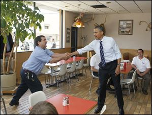 President Obama shakes hands with unidentified man at Rudy's Hot Dogs.