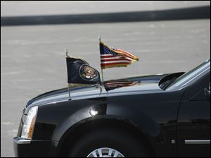 A presidential Cadillac with the U.S. flag and the presidential flag.