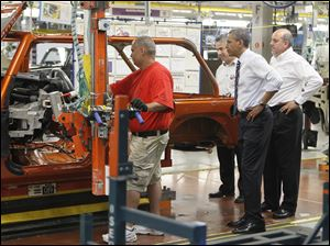 President Obama examines how a Jeep employee works on the assembly line while on his visit to the Jeep Wrangler plant at Chrysler Group LLC's Toledo Assembly complex.