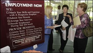 Glynis Davies, left, from Hartman Personal Services, talks with job seekers Christine Marciante and Maxine Janke, right, at the Jobapalooza job fair May 25 at Lake Erie College, in Painesville, Ohio.