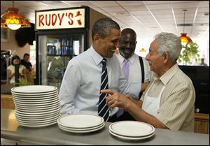 President Barack Obama visits Harry Dionyssiou at Rudy's Hot Dog at 946 W. Sylvania Ave., Toledo, on Friday as Toledo Mayor Mike Bell looks on.