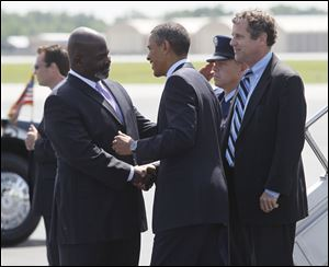 Toledo mayor Mike Bell greets President Barack Obama at Toledo Express Airport on Friday. At right is Ohio Sen. Sherrod Brown.