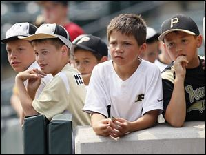 Young Perrysburg fans, two sporting rally caps, watch as Perrysburg loses 6-2 to Lakota East in the Division I state baseball championship game in Columbus.