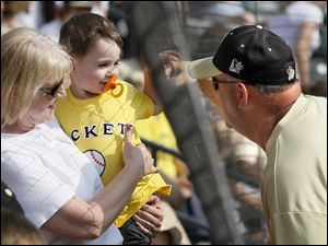 Perrysburg coach Dave Hall bumps hands with his grandson Landon Eddy, 2, of Cuyahoga Falls, Ohio, being held by his wife and Landon's grandmother, Debbie Hall, prior to the Division I state baseball championship game against Lakota East in Columbus.