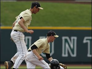 Perrysburg second baseman Alec Schmenk (3) left, and shortstop Kevin Schenk watch the throw go into the outfield as Lakota East's Evan Hills steals second base during the second inning.