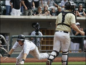 Lakota East's Craig Thomson scores in the fourth inning.  Perrysburg catcher Zach Kolvey is at right.