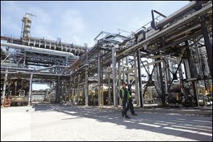 Employees walk through the grounds at the Husky Lima Refinery, a 1,100- acre complex that employs 430 hourly workers.