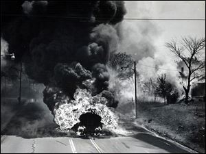 A trailer of a Standard Oil tanker truck carrying 7,900 gallons of gasoline, burns after overturning on the Trail near Vinton Street in South Toledo on June 10, 1961.