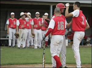 Bedford's Jackson Lamb (7) is met at the plate by teammates after hitting a home run.