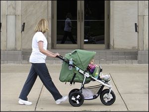 A woman pushes a child in a stroller in Parma, Ohio.