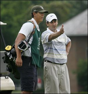 Caddie Derrick Creque talks strategy with golfer Jeff Judis at Toledo's Inverness Club, where there are 300 caddies on staff. Creque is one of several Evans Scholars at the club. He attends Miami University.