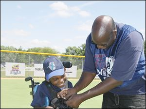 James Anderson, right, helps his son Keontaye Anderson, 11, to put his mitt on in the outfield.