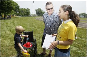Connor Bell, 6, and his dad, Dave, talk with Inside Angles employee Amber Wilkie, right. Connor, who has osteosarcoma, a cancerous bone tumor, was the inspiration for the lengthy lemonade stand.