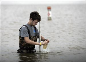 Scott Denham II of the University of Toledo Lake Erie Center takes a sample from Lake Erie at Maumee Bay State Park in Oregon. The sample will go to the lab.