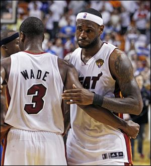 Miami Heat's LeBron James hugs teammate Dwyane Wade (3) after Game 6 of the NBA finals against the Dallas Mavericks.