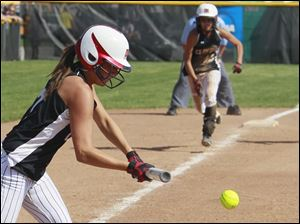 Clinton's Megan Oberst (7) bunts home Haley Mercy (12) during the third inning against Blissfield.