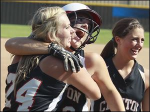 Clinton's Abi Clark (9) celebrates hitting a grand slam in the fourth inning against  Blissfield with Ashley Thompson (24) and Keely Quiring (20).