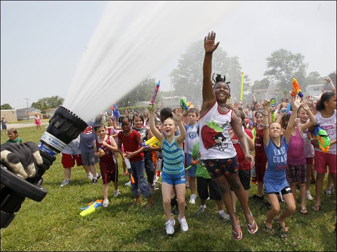 Shania Pippens Students at Manor School in Monroe, Mich., including Shania Pippens, 7, jumping, cool off in the spray from a Monroe Fire Department hose.
