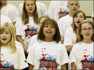 Sixth-graders including, from left, Morgan Moore, Jada Jones, and Lexi Steinmetz, sing