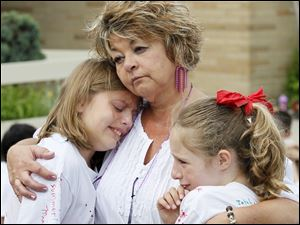Beth Johnston, a third-grade teacher at Smith Road Elementary, comforts students Clara Gill, 9, left, and Daelyn Perez, 9.
