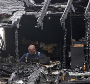 A firefighter sifts through the remains of an early morning house fire in Warren, Ohio, that killed six people Thursday.