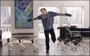 Jim Carrey dances with his penguins in the film 'Mr. Popper's Penguins.'