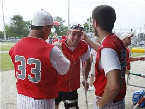 Bedford assistant coach Jack Eaton, left, injured catcher Jared Kujawa, center, and Troy Przybylek, celebrate after the Mules beat Sterling Heights Stevenson in the Michigan High School Division 1 state baseball semifinal.