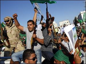 In this photo taken on a government-organized tour an armed Libyan security officers sit on top of a car as people rally at the Green Square in Tripoli, Libya, on Friday.