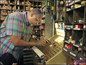 Bennie Summers tests a tube in his shop at Summertyme Vintage Radio Repair in the Maumee Antique Mall.