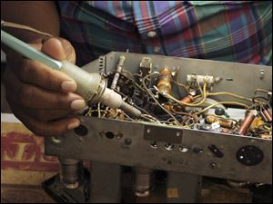 Bennie Summers solders a part in an old radio.