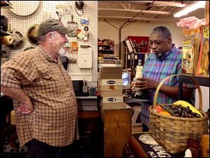 Bennie Summers examines a Champion Spark Plug radio that Terry Hood, of Swanton, brought to Summertyme to be repaired.