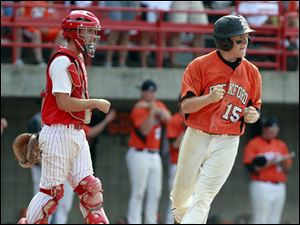 Bedford catcher Troy Przybylek (23) watches as Rockford's Brandon Nostrant (15) scores the winning run.