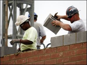 Masonry workers lay bricks on a new building that will be in a Fremont Pike strip mall.
