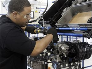 Larry Patterson, of Ypsilanti, attaches the wiring block to the rear of an engine at Chrysler's Dundee plant.