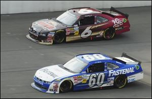 Carl Edwards (60) passes teammate Ricky Stenhouse Jr. with less than 10 laps remaining on his way to winning the NASCAR Nationwide Series Alliance Truck Parts 250 at Michigan International Speedway.