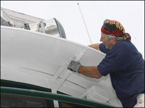 John Georgakopoulos, Liberty Center, paints the vessel. The Willis B. Boyer is being restored by workers from P & W Painting Contractors Inc. to recreate the Great Lakes freighter the S.S. Col. James M. Schoonmaker out of the S.S. Willis B. Boyer.
