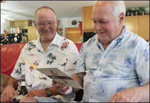 David Sowards watches his brother Daniel Miller read the card he gave him in Florida for his 70th birthday.