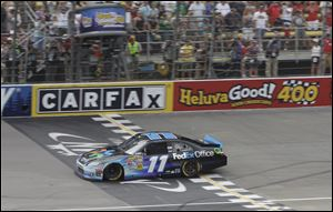 Denny Hamlin crosses the finish line to win the NASCAR Sprint Cup Series auto race at Michigan International Speedway in Brooklyn, Mich. on Sunday.
