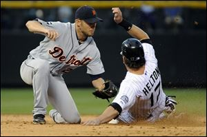 Tigers shortstop Jhonny Peralta (27) tags out the Rockies' Todd Helton (17) at second during the sixth inning.
